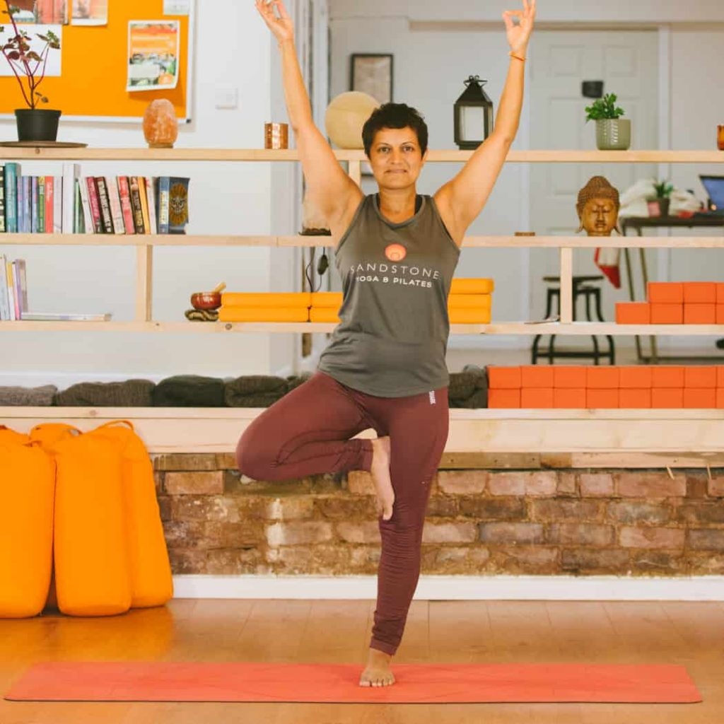 Woman in yoga pose in front of book case with orange yoga pillows in background