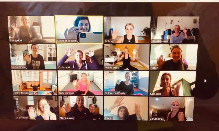 Yoga Zoom call showing everyone sitting on mats, waving on their individual screens